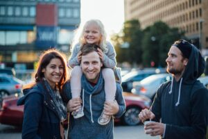 Image of a smiling family standing on a street in Helsinki. The man is carrying a little blond girl on his shoulder and next to the family stands another man with a coffee in his hand